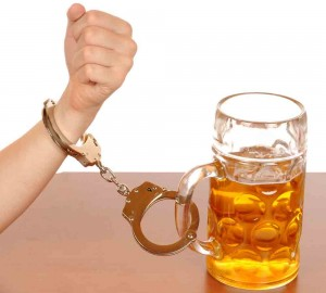 Glas of beer with handcuffs as symbol for alcohol abuse